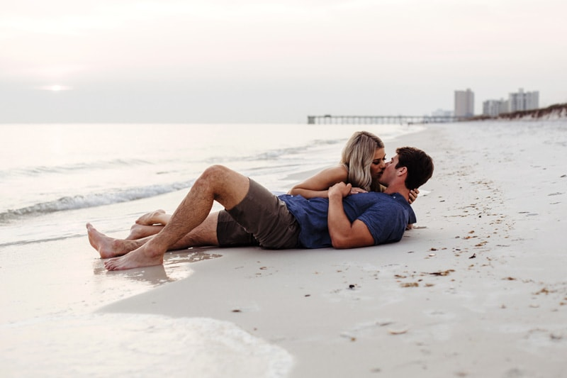 Couples Photography Jacksonville Beach Florida, couple kissing on beach laying in the sand